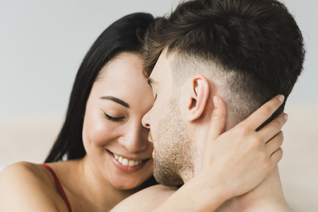 attractive, happy asian woman tenderly embracing handsome boyfriend with closed eyes Reklamní fotografie