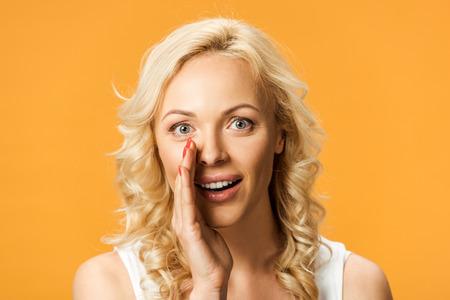 Jolie femme blonde regardant la caméra et les commérages isolés sur orange Banque d'images