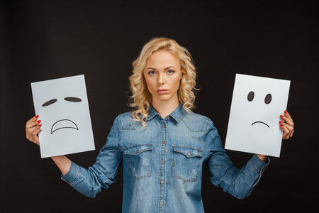 upset blonde woman holding cards with sad emotions on black