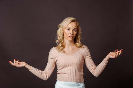 beautiful blonde woman showing shrug gesture isolated on black