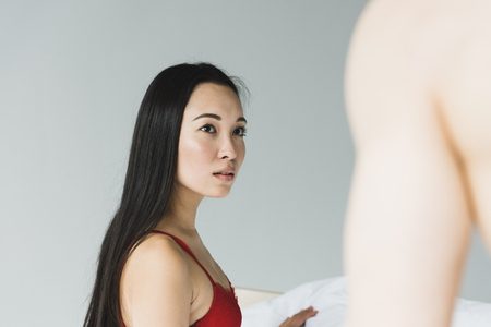 pensive, beautiful asian woman in red bra looking at shirtless boyfriend