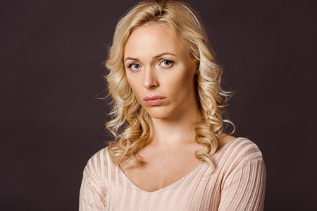 upset blonde woman looking at camera isolated on black