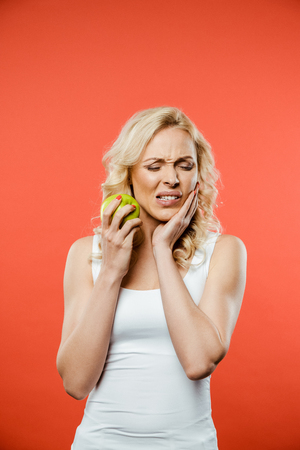 attractive woman with closed eyes holding green apple while having toothache on red Banco de Imagens