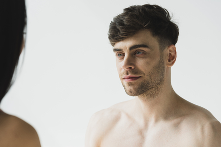 handsome, pensive shirtless man tenderly looking at girlfriend on grey