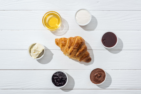 Flat lay of bowls with cream cheese, chocolate cream, sour cream, jam and honey near fresh croissant on white background