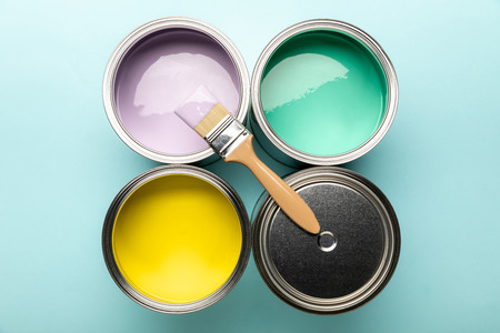 Top view of tins of paints and brush on blue surface Stockfoto
