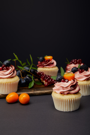 cupcakes with cream, fruits and berries on grey surface isolated on black