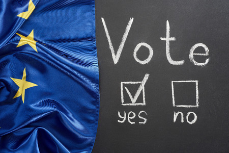 Top view of vote lettering and check mark near yes word on black chalkboard near European flag Imagens