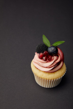 Cupcake with garnet, blackberry and grape on black surface
