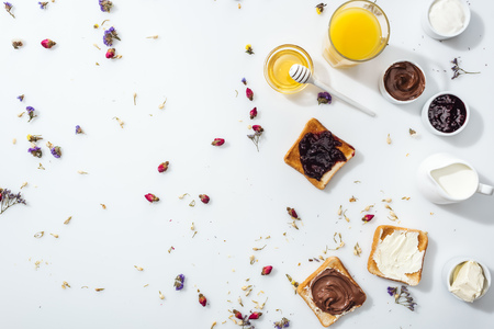 Top view of tasty toasts with jam, chocolate cream and cream cheese near honey and glass of orange juice on white background Banque d'images - 122291887
