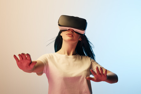 Selective focus of girl in white t-shirt wearing virtual reality headset and gesturing on beige and blue background