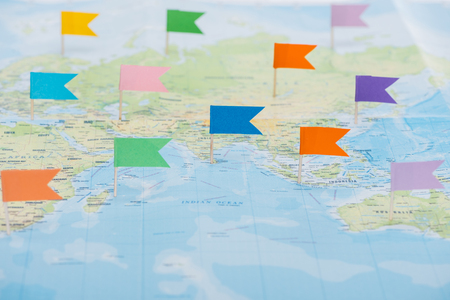 Colorful stationery flags pinned on world map