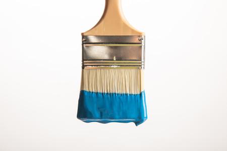 Houten borstel met blauwe verf die op witte achtergrond wordt geïsoleerd