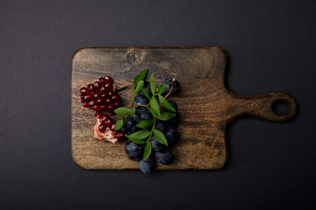 Top view of grapes and garnet on wooden cutting board on black surface 写真素材