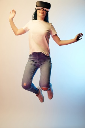 Cheerful young woman in virtual reality headset jumping and gesturing on beige and blue background