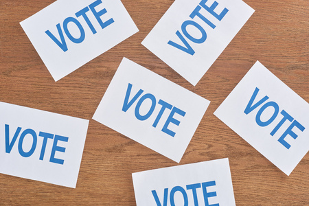 Top view of white cards with blue vote lettering scattered on wooden table background