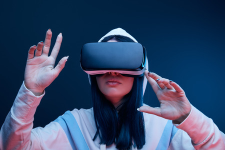 Brunette girl in hood gesturing while virtual reality headset on blue background