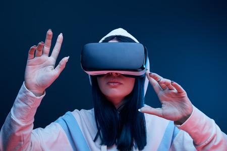Ragazza bruna in cappa che gesticola mentre le cuffie da realtà virtuale su sfondo blu