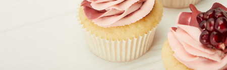 Panoramic shot of cupcakes with cream and garnet on white surface