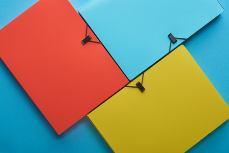 Top view of arranged colorful paper folders on blue background Imagens