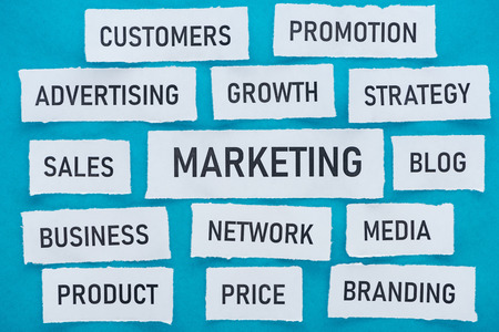 Top view of components related to marketing on pieces of paper on blue background Stock Photo