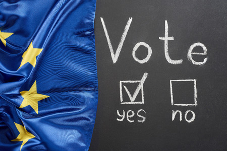 Top view of vote lettering and check mark near yes word on black chalkboard near flag of Europe 스톡 콘텐츠