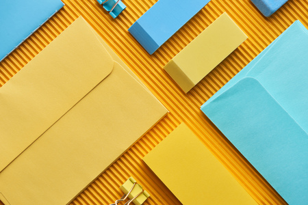 Top view of sticky notes, envelopes and erasers on yellow background