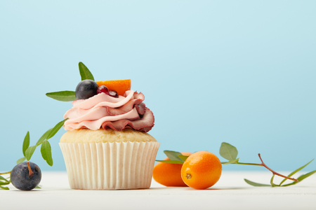 Tasty cupcake with cream and kumquats on white surface isolated on blue background
