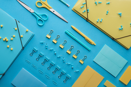 Top view of various colorful stationery isolated on blue background