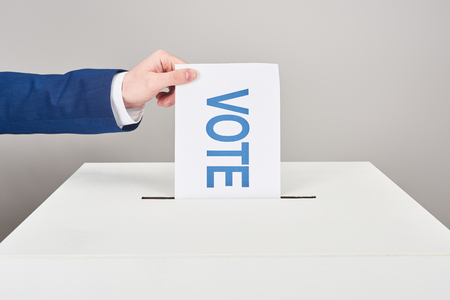 Cropped view of man putting card with vote in box on grey background