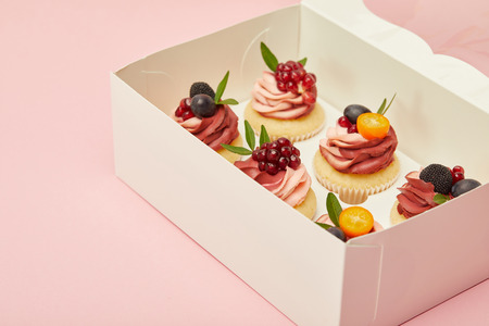 sweet cupcakes with berries and fruits isolated on pink 写真素材
