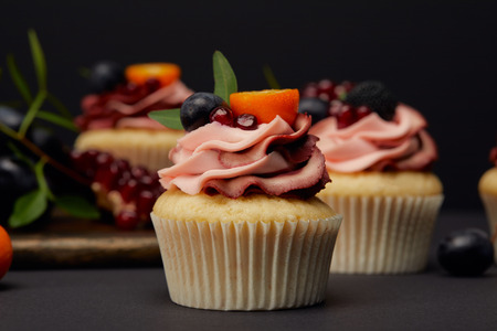 Cupcakes with fruits and berries on grey surface isolated on black background