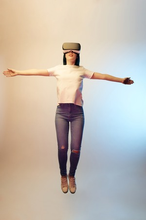 young woman in virtual reality headset with outstretched hands levitating on beige and blue