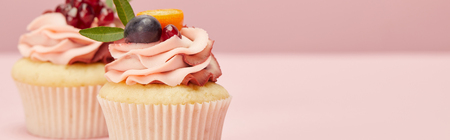 panoramic shot of sweet cupcakes with berries and fruits on pink surface Banco de Imagens