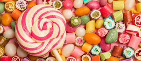 Panoramic shot of bright round lollipop on wooden stick near fruit caramel candies on pink background