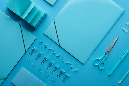 Flat lay of paper binders and various arranged stationery isolated on blue background Stock Photo