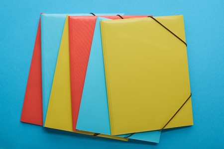 Top view of arranged red, blue and yellow paper binders 版權商用圖片