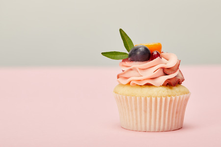 Tasty cupcake with cream and fruits on pink surface isolated on grey background