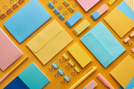 Flat lay of colorful arranged office stationery supplies on yellow background