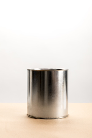Tin of paint on beige surface on white background