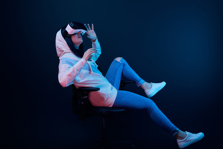 surprised girl gesturing and using virtual reality headset while sitting on chair on blue