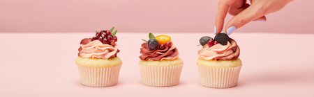 Panoramic shot of woman with cupcakes on pink surface Stock Photo