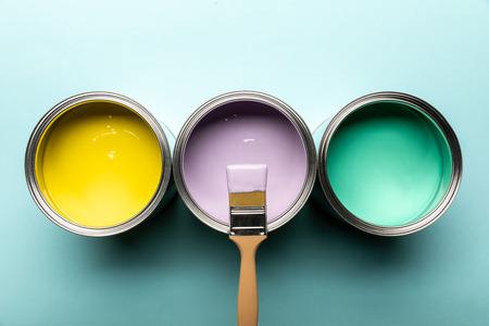 Vista superior de tres latas con pinturas y pincel sobre superficie azul