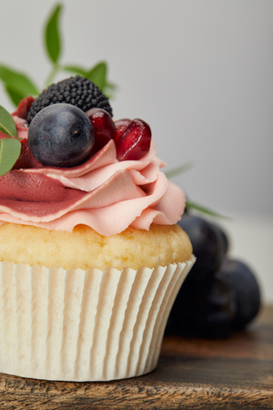 Tasty sweet cupcake with berries on wooden cutting board 写真素材