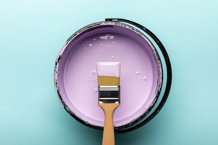 Top view of bucket with purple paint and brush on blue background