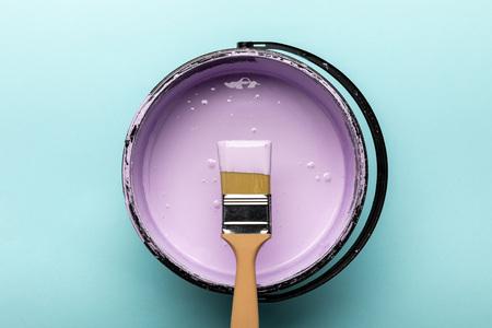 Vue de dessus du seau avec peinture violette et pinceau sur fond bleu