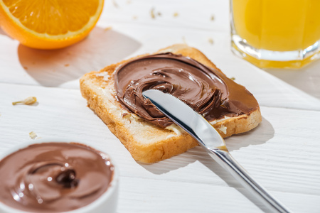Selective focus of toast with chocolate cream near knife and half of orange on white background Banque d'images - 122292129