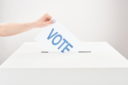 Partial view of woman putting vote in box on grey background