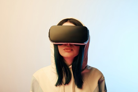 Attractive brunette woman in virtual reality headset on beige and blue background