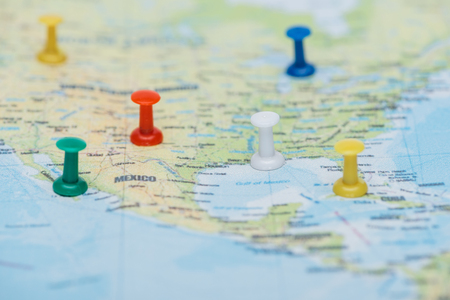Close up view of colorful push pins on world map